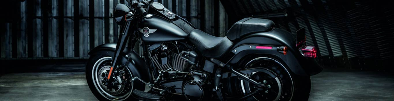 A close-up of a black  Harley-Davidson motorcycle in a dark garage.