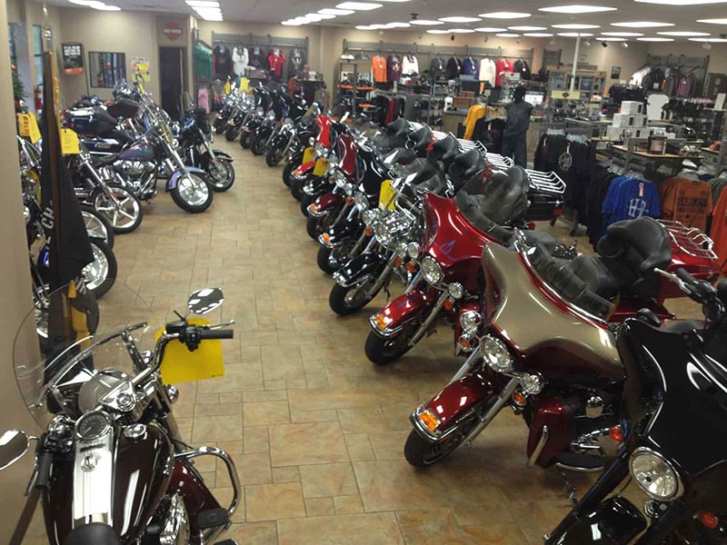 A row of pre-owned motorcycles on the showroom floor.